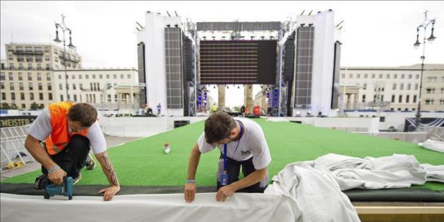 Dos operarios trabajan en las instalaciones colocadas para recibir mañana a la selección de fútbol alemana tras alzarse campeones del mundo frente a Argentina, frente a la Puerta de Brandenburgo, Berlín, Alemania. (EFE)